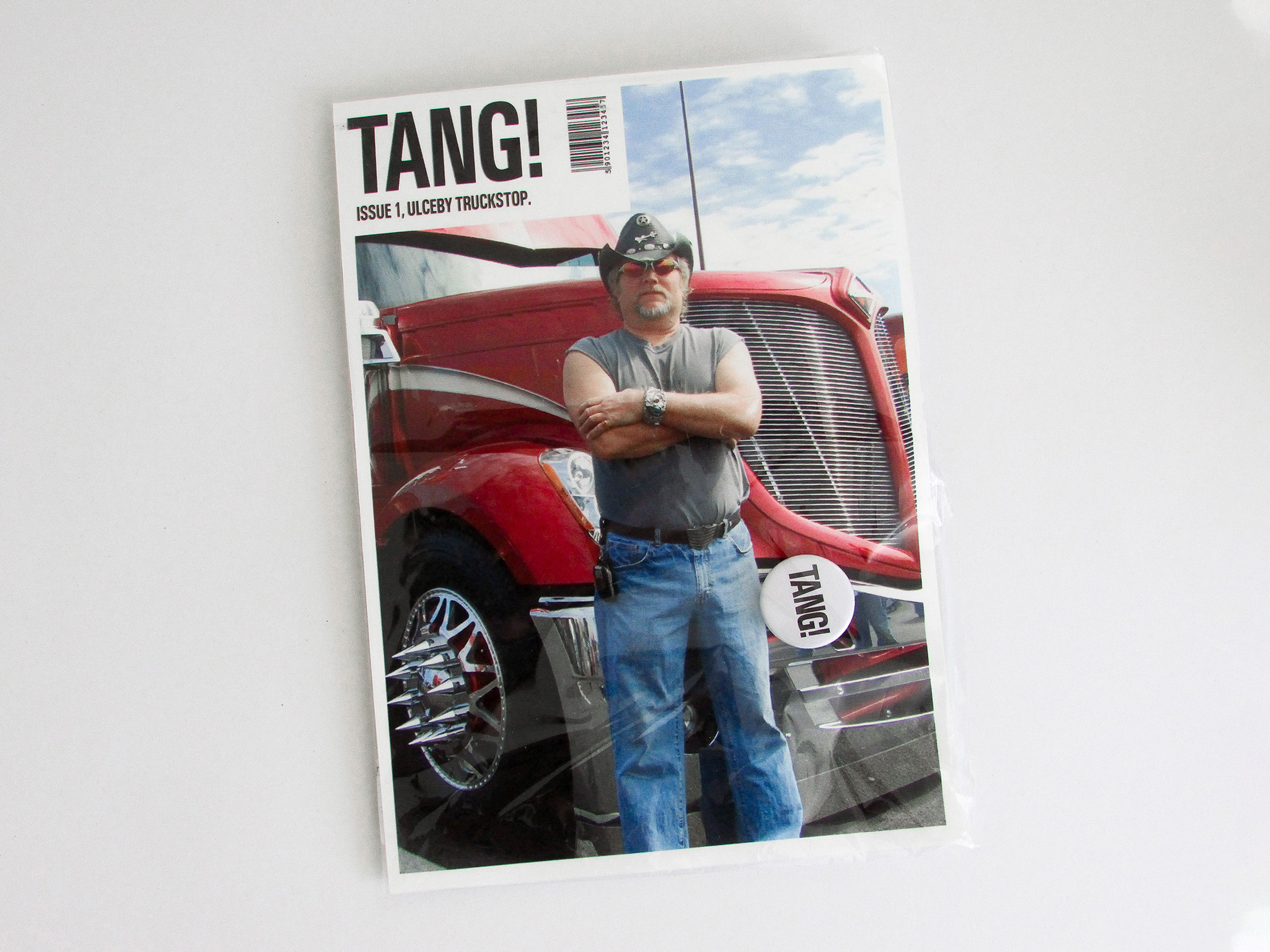 publication cover featuring a photograph of a truck driver standing in front of his truck